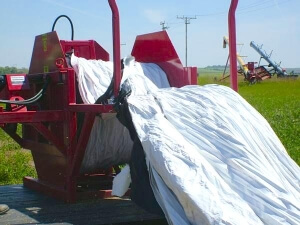 Rolling a grain bag for recycling at Unity, SK.