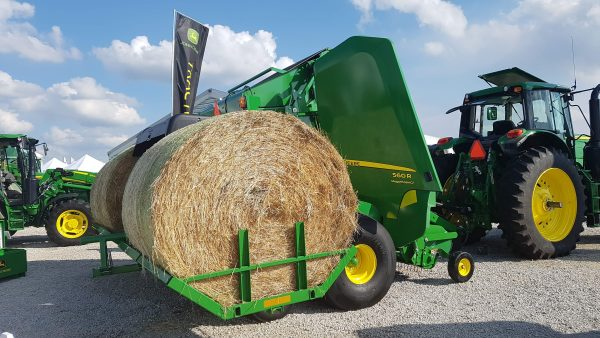 A John Deere 560 round baler equipped with a new A520R Plus2 Accumulator carries two round bales behind the baler while the third is made in the chamber. (Photo: Kelvin Heppner, 2017)